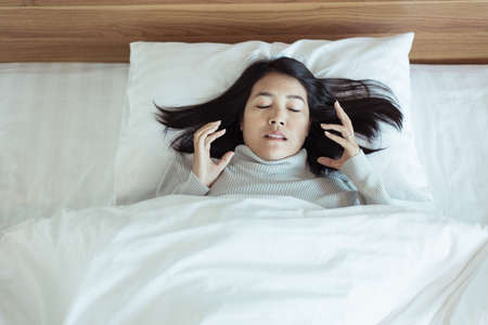 Bad dream or Nightmare,Asian woman with scared and panic while lying down under the blanket in bedroom