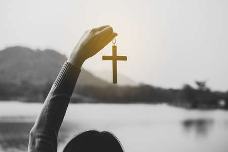 Mano de mujer sosteniendo la cruz crucifixión de Jesucristo en la naturaleza, en tonos de blanco y negro