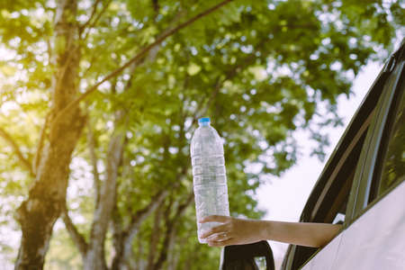 Global warming environmental protection concept,Woman hand holding plastic bottle on the road
