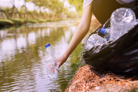 Woman volunteer picking up a bottle plastic trash in river,Environment and pollution campaign concept