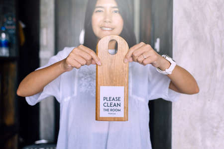 Woman hands holding please clean the room sign of hotel room