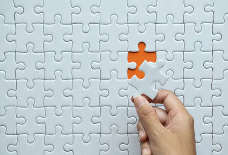 Pieces of jigsaw puzzle in woman hands,Jigsaw puzzle white color,Puzzle pieces grid,Success mosaic solution template,Horizontal on orange background copy space for text,Top view Banque d'images