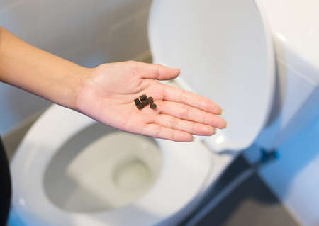 Woman hands holding laxative pill and using toilet and suffers from diarrhea and hemorrhoids after wake up in the morning Stock Photo