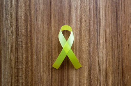 Yellow ribbon on wooden background, Top view