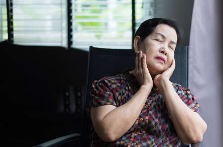 Elderly asian woman sitting near the window at home,Senior having sorrowful and depressed