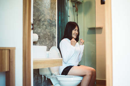 Asian woman sufferring with Hemorrhoids or constipation in toilet,Female need to use the toilet in the morning