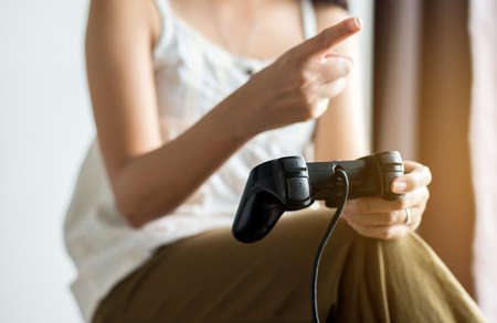 Close up of hand woman playing video games at home,Women holding joystick
