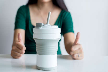 Blured woman showing thumb up with reusable coffee mug,Healthy green,Zero waste,Environmental friendly,Conscious lifestyle concept