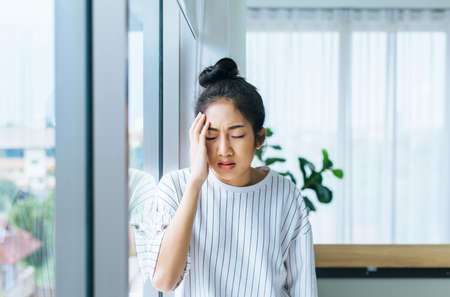 Asian woman having a headache in bedroom,Women suffering from migraine at home Stok Fotoğraf