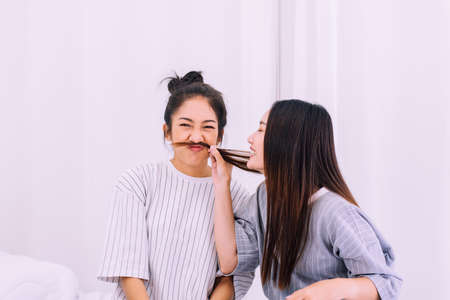 Two beautiful asian women are having fun and making fake mustaches from hair,Happy and smiling