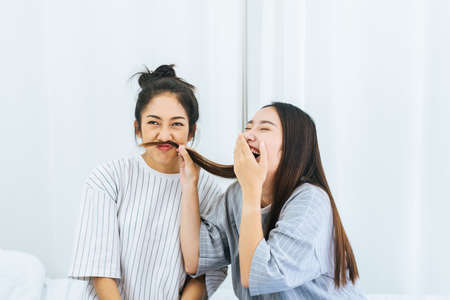 Two beautiful asian women are having fun and making fake mustaches from hair,Happy and smiling Banque d'images