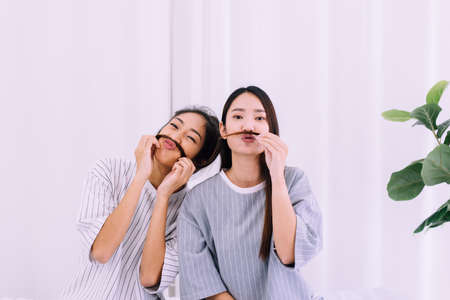 Two beautiful asian woman are having fun and making fake mustaches from hair,Happy and smiling,Best friend