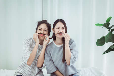 Couple beautiful asian women are having fun and making fake mustaches from hair,Happy and smiling