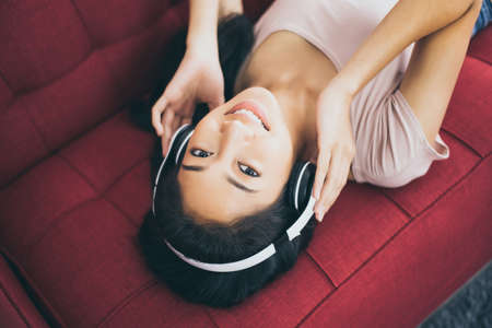Beautiful young asian woman listening to music with headphones while lying on sofa Stok Fotoğraf
