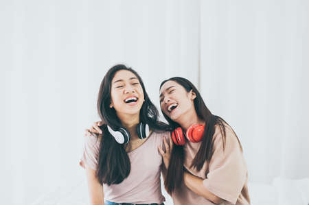 Cheerful couple young woman listening to music together at home