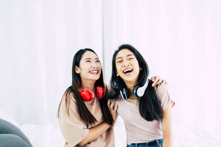 Two young asian women laughing in the living room,Happy and smiling