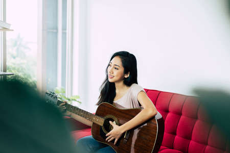 Beautiful young asian woman playing guitar while sitting on sofa in living room at home Stok Fotoğraf