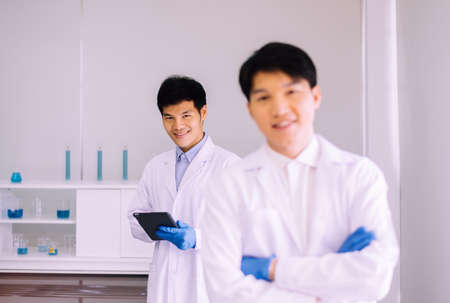 Asian man scientist or doctor standing and working with tablet in hospital,Professional medical teamwork