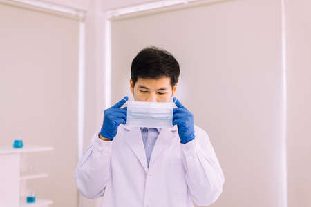 Man doctor or scientist wearing facel mask for protective coronavirus in laboratory Stok Fotoğraf