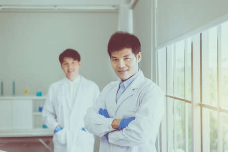 Asian man scientist posing with arms crossed working in hospital,Professional medical teamwork