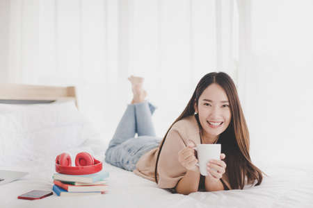 Happy asian beautiful woman drinking coffee on the bed in home