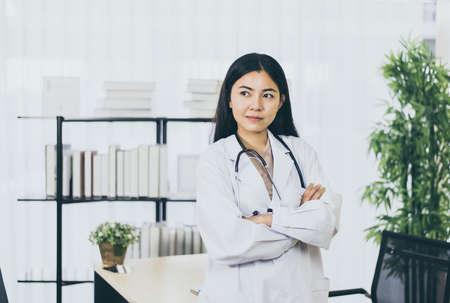 Portrait of young asian doctor woman in white coat standing in hospital