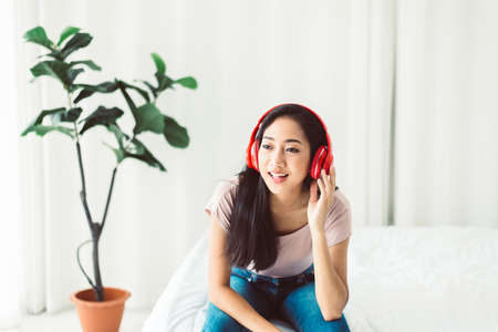 Beautiful young asian woman laughing and looking to camera while sitting in bedroom Stok Fotoğraf