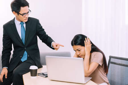 Asian man boss pointing finger to stressed woman employee in office Stok Fotoğraf