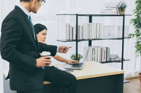 Asian man boss pointing finger to a stressed woman employee in office