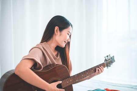 Happy young asian woman playing guitar in bedroom at home