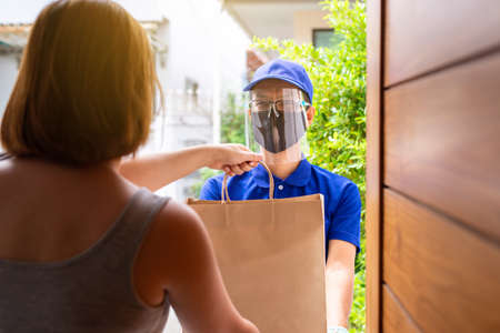 Delivery asian man holding paper bag prepare send to woman customer at home