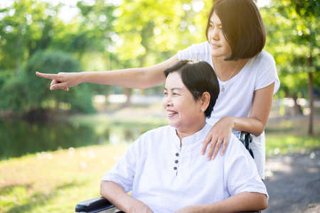 Caregiver take care to elderly asian woman sitting on wheelchair at nature,Senior care insurance concept 免版税图像