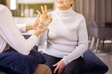 Sign language specialist talking with mature patient deaf hearing and showing hands gesture Imagens