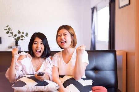 Cheerful couple asian women watching TV feeling having fun together at home Foto de archivo