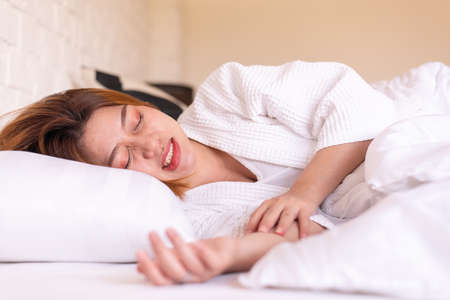 Asian woman sleeping on the bed and grinding teeth,Female tiredness and stress Imagens