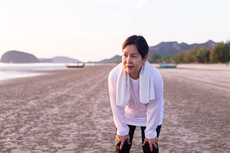 Elderly asian woman break and relax after workout at the beach in the morning