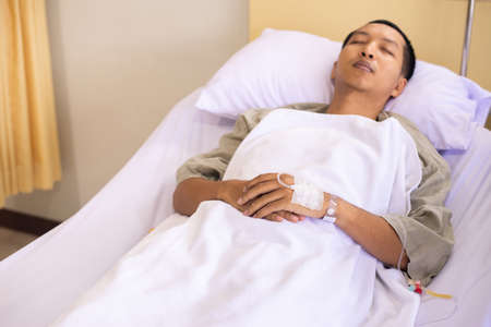 Patient Asian man sleeping under blanket on sick bed at the hospital