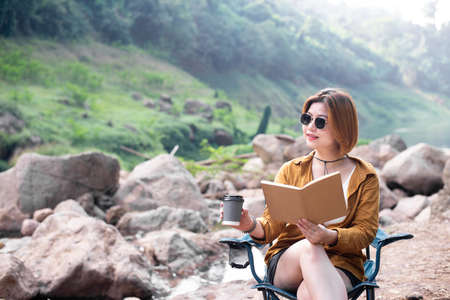 A solo woman traveller reading book while sitting on chair at waterfall Stock Photo