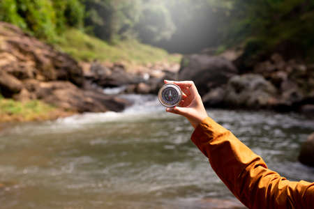 Hands traveler solo woman holding compass at waterfall,Navigation for travel