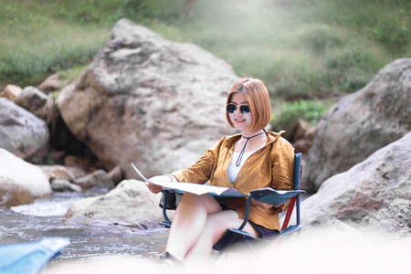 Happy solo woman traveller reading map while sitting on chair at waterfall