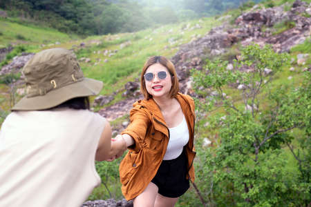 Tourist asian woman getting help to friend climb a rock,Helping hands,Overcoming obstacle concept