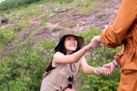 Tourist asian women getting help to friends climb a rock,Helping hands,Overcoming obstacle concept Stock Photo