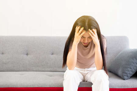 Depression asian woman have a headache or migraine of lonely sitting on sofa at home,Female under a lot of pressure,Mental health care concept,World mental health day,Suicide prevention Stock Photo