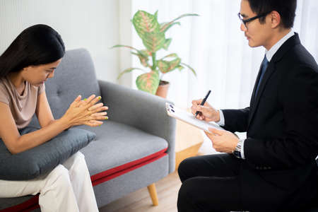 Professional psychologist talking with asian woman patient,Therapist man conducting a consultation and counseling Stock Photo