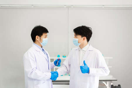 Successful and research working scientists man shake hands together in laboratory
