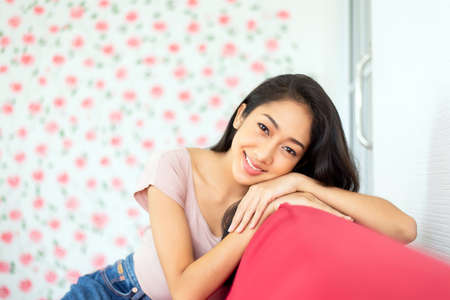 Beautiful young asian woman happy and smiling face and looking to camera sitting on sofa