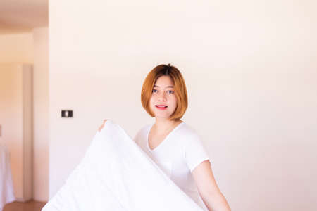 Make a bed,Asian women making her bed in room after wake up