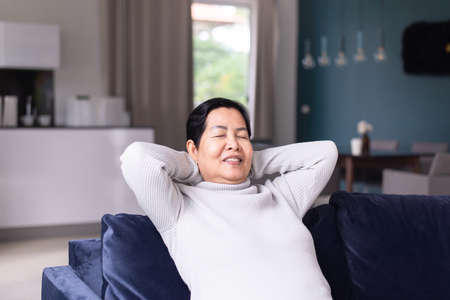 Elderly asian woman sitting on couch in living room with hands over head,Relaxing time