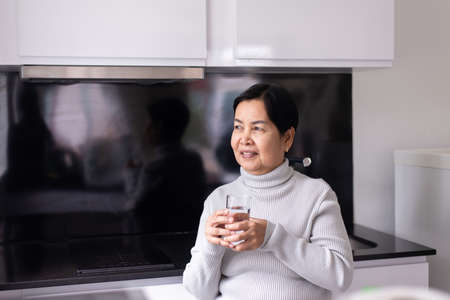 Mature asian woman drinking water at home in the morning,Happy and smiling,Elderly healthy care concept Imagens