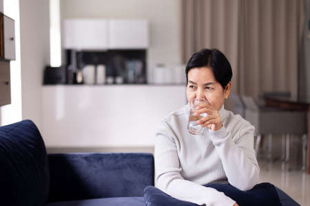 Elderly asian woman drinking water at home in the morning,Happy and smiling,Senior healthy care concept